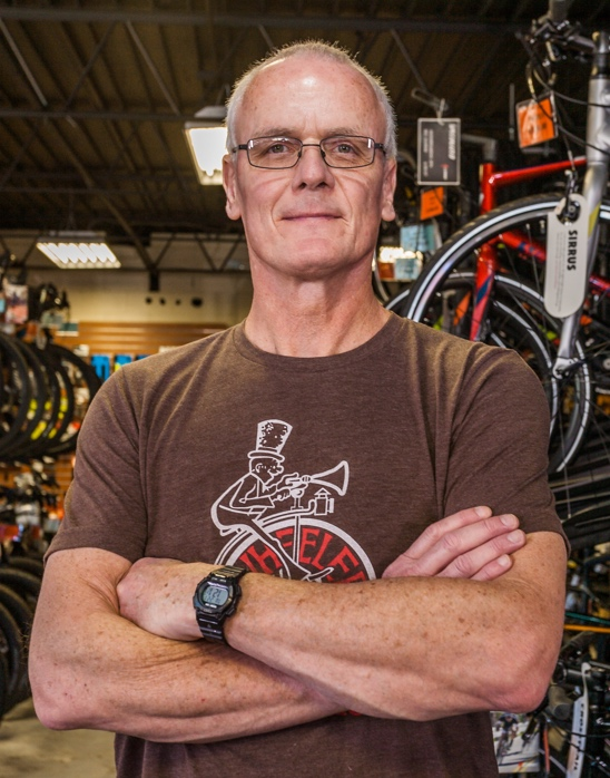 Steve G, Bicycle Shop Owner, stands assuredly with arms crossed