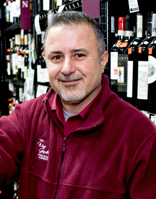 Tony B, Wine Store Owner, toasts with a glass of red wine